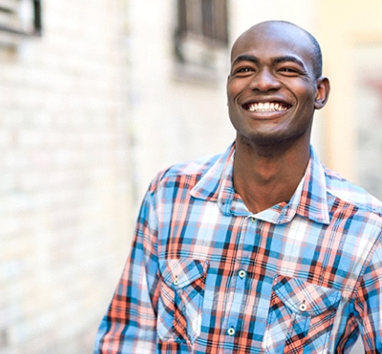 A young man wearing a plaid shirt and smiling while outside