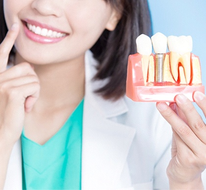 A woman pointing to her smile and holding a mold with a single tooth implant