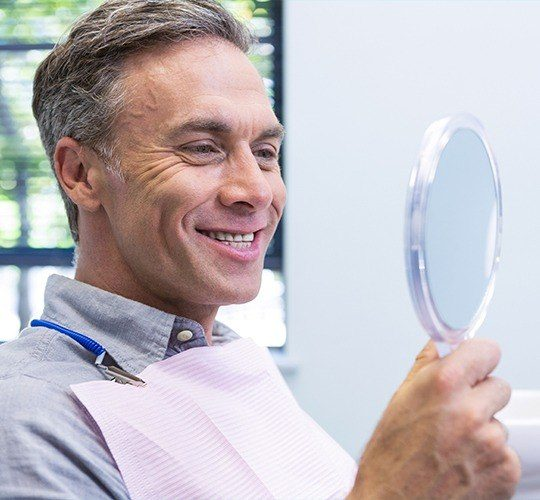 man smiling in circle mirror