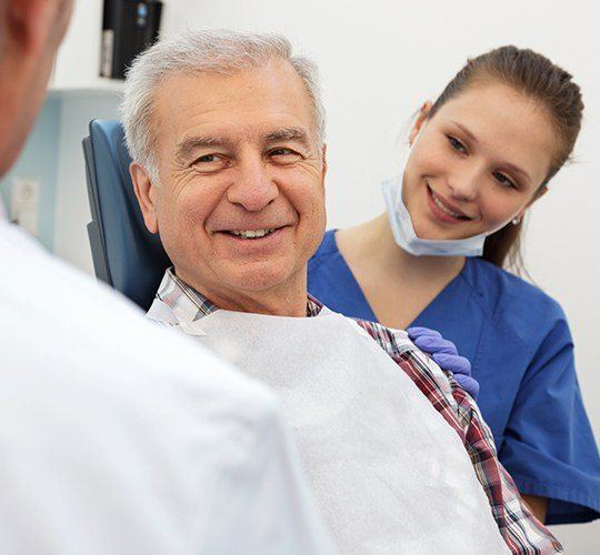 older man smiling at dentist
