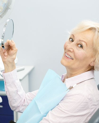 An older woman holding up a mirror at the dentist's office after having her dental implants in Westport put into place
