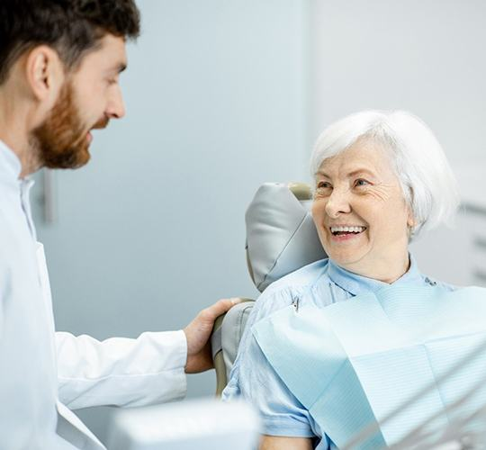 An older woman smiling at her dentist during an examination after receiving her dental implants