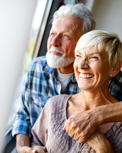 An older couple smiling while looking outside and holding hands after receiving their dental implants in Westport