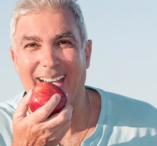 An older gentleman smiling while preparing to bite into a red apple