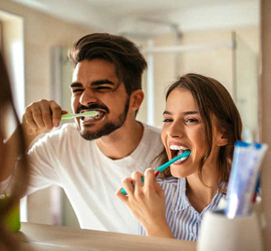 A man and woman brushing their teeth in the mirror as a way to care for their veneers