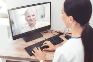 a female dentist providing teledentistry services for an elderly patient