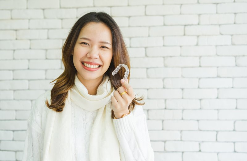 woman holding Invisalign aligner and smiling