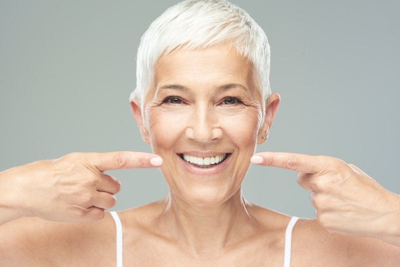 older woman pointing to fully restored smile